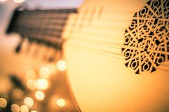 stock image of  lute with instrumental sheet music and soft lights for christmas holiday, split tone