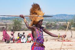 stock image of  maasai man, warrior, typical garb and male lion mane on head, spear in hand, tanzania
