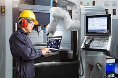 stock image of  maintenance engineer using laptop computer control automatic rob