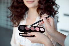 stock image of  makeup artist applies eye shadow. perfect smooth skin.applying makeup. application of shadows on the model`s eyes