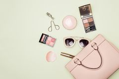 stock image of  makeup products with cosmetic bag on color background