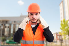 stock image of  male constructor doing hear no evil gesture