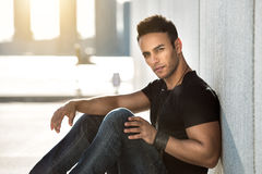 stock image of  male fashion model man in black t-shirt, dark blue jeans and leather bracelet posing outdoors.