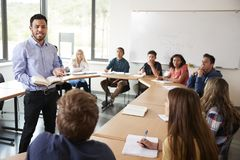 stock image of  male high school tutor with pupils sitting at table teaching maths class