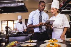 stock image of  male manager and female chef using digital tablet in kitchen