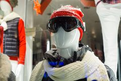 stock image of  male mannequin in store window during winter with ski gear, woolly hat, dark goggles, scarf, down jacket and fake snow on head