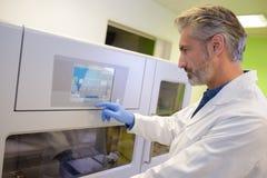 stock image of  male medical technician programming machine