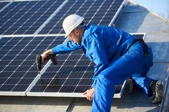 stock image of  electrician mounting solar panel on roof of modern house