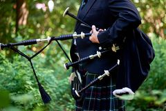 stock image of  a man with a bagpipe, a kilt in a cage with a green and red stripe. culture. the details of the skirt of the kilt and