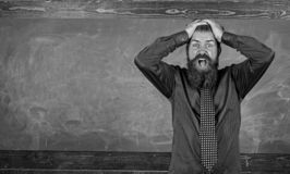 stock image of  man bearded teacher or educator hold head chalkboard background. pay attention to your behaviour and manners. teacher