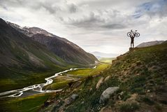stock image of  man with bike in the mountain
