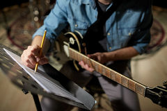 stock image of  man with guitar writing to music book at studio