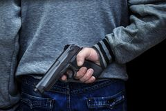 stock image of  man holding a gun behind his back against a black background. concept of danger, crime