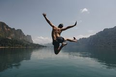 stock image of  man jumping with joy by a lake