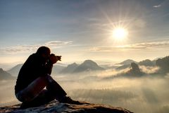stock image of  man photographer hike. photographer taking photos outdoor by dslr camera. travel lifestyle