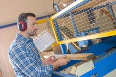 stock image of  man putting wood into machine