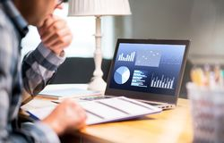 stock image of  man reading business report paper. laptop with financial graphs