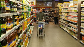stock image of  man with shopping cart walking in the hypermarket