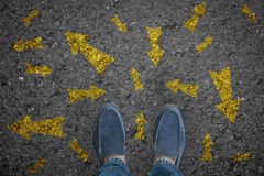stock image of  man standing on road with many direction arrow choices or move