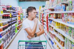 stock image of  man in the supermarket, customer thinking, choose what to buy