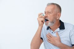 stock image of  man using asthma inhale