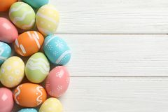 stock image of  many colorful painted easter eggs on wooden background, top view.