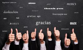 stock image of  many thumbs up with the word `thank you` in many languages in front of a blackboard