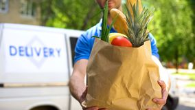 stock image of  market worker giving grocery bag, goods delivery service, express food order