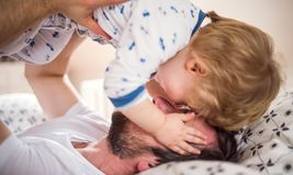 stock image of  father with a toddler boy having fun in bedroom at home at bedtime.
