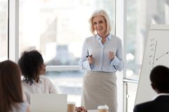 stock image of  mature female business coach speaking at team meeting training s
