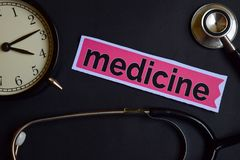 stock image of  medicine on the print paper with healthcare concept inspiration. alarm clock, black stethoscope.