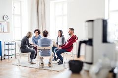 stock image of  men and women sitting in a circle during group therapy, talking.