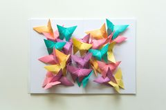 stock image of  mental health concept. colorful paper butterflies sitting on book in shape of butterfly. harmony emotion. origami. paper cut style