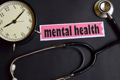 stock image of  mental health on the paper with healthcare concept inspiration. alarm clock, black stethoscope.