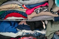 stock image of  messy folded clothes crammed in a closet on a shelf. depicting woman`s wardrobe, consumerism, cleaning up, tidying up, purging, et