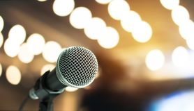 stock image of  microphone on abstract blurred of speech in seminar room or speaking conference hall light, event concert bokeh background
