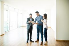 stock image of  couple signing sale purchase agreement by broker in new home