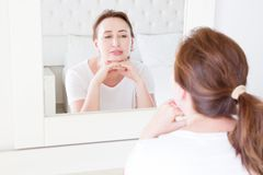 stock image of  middle age woman looking in mirror on face. wrinkles and anti aging skin care concept. selective focus