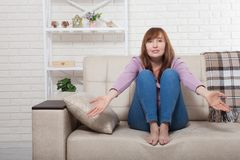 stock image of  middle aged beautiful brunette woman confused at home background. menopause