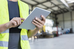stock image of  midsection of manual worker using digital tablet in metal industry