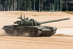 stock image of  military or army tank ready to attack and moving over a deserted battle field terrain.