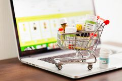stock image of  mini shopping cart full of different homeopathic remedies on laptop background.