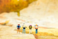 stock image of  miniature people: travelers with backpack standing on world map, walking to destination. image use for travel business concept