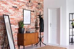 stock image of  mirror next to wooden cabinet in entrance hall interior with white door and poster on red brick wall
