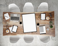stock image of  mock up poster frame on meeting conference table with office accessories and laptop computers, hipster interior background,