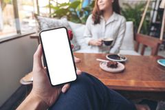 stock image of  a man`s hand holding black mobile phone with blank white screen with woman sitting in cafe