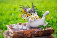 stock image of  mortar of healing herbs, bottles of homeopathic globules and old book outdoors.