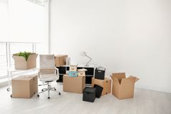 stock image of  moving boxes and furniture in office