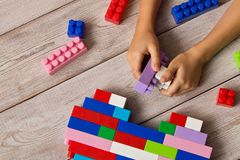 stock image of  multi-colored plastic constructor in the hands of the girl. children`s educational games