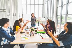 stock image of  multiethnic diverse group of creative team or business coworker clap hands in project presentation meeting leading by asian woman